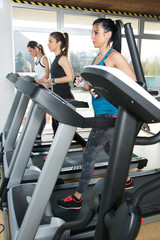 Three young women running on treadmill in gym.