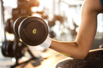 Close up of young sporty woman with heavy steel dumbbell.