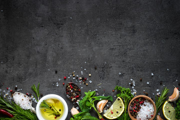 Selection of spices herbs and greens. Rosemary basil lemon olive oil pepper top view black...