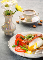 Delicious, healthy and nutritious breakfast with egg poached whole-grain toasted bacon tomatoes and coffee with almonds