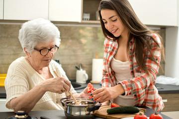 Oma en kleindochter koken in de keuken.