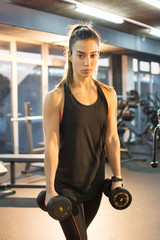 Young sporty woman with weights in gym.