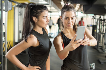 Two female friends taking a selfie photo at gym.