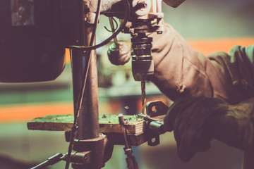 Worker drilling holes in a steel part. Small metal manufacture of   steel accessories.