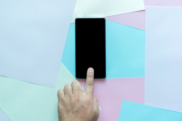 man hand holding the phone tablet on color paper background