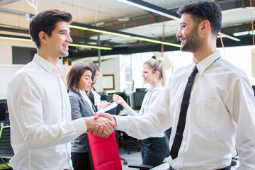 Two smiling businessmen shaking hands while standing in the office together with business people in the background.