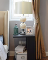 decorative table lamp on black wooden table in bedroom interior