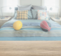 wooden table top with blur of bedroom with decorative pillow and football on bed