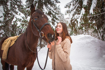 Young girl and horse in a winter forest