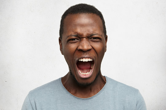 Human facial expressions, emotions and feelings. Portrait of mad angry young dark-skinned male dressed casually, screaming in anger and fury with mouth wide open while being fed-up with something