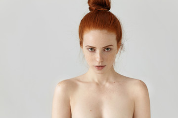 People, youth and beauty. Isolated portrait of attractive young Caucasian female with ginger hair knot posing topless indoors, having freckles all over her face and shoulders, staring at camera