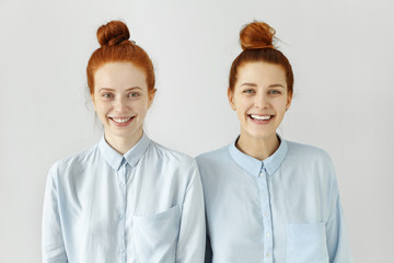 Studio shot of two Caucasian siblings with same ginger hair buns, wearing similar light-blue t-shirts, smiling happily, looking at camera, posing at white blank wall, standing to each other closely