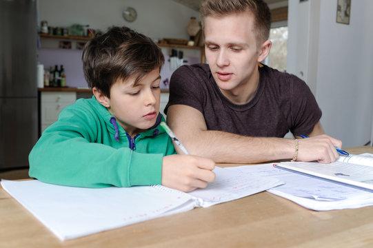 Schüler bekommt zuhause Nachhilfeunterricht in Mathematik von einem Studenten