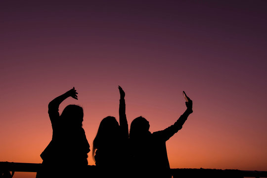 Silhouette of friend enjoying for selfie