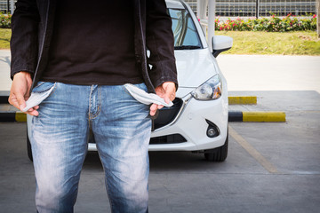 Man showing his empty pockets with white car background.