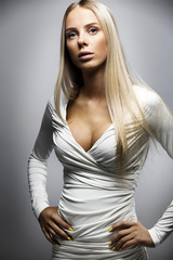 Confident fashion portrait of a blonde woman in white dress