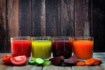 Four glasses of healthy vegetable juice with scattered vegetables and a dark wood background