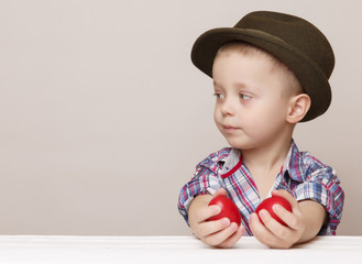 Tiny little boy in a hat looks left in hands holding red Easter eggs. Copy Space.