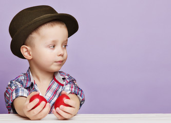 Tiny little boy in a hat looks right into the hands holding red Easter eggs. Copy Space.