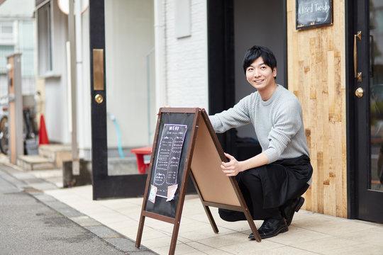看板を出すカフェ店員