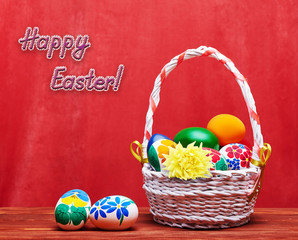 Braided Easter basket with colored eggs on a red background