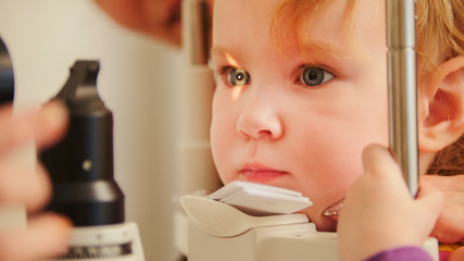 Child's optometry concept - little girl checks eyesight in eye ophthalmological clinic
