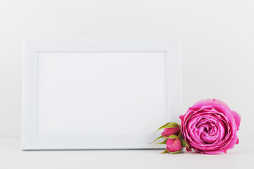 Mockup of picture frame decorated rose flower on white desk with clean space for text and design your blogging.