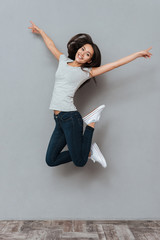 Vertical image of pretty happy woman jumping in studio