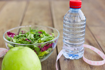 Green salad in glass bowl, measuring tape, green aplle and still water in the bottle.