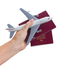 Plane travel concept, hand holding passports with plane isolated on white background