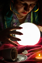 Fortune teller predict future and looking at shining crystal ball