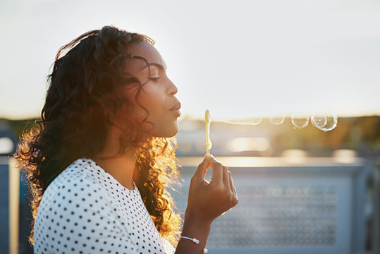 Attractive woman blowing soap bubbles