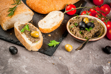 Homemade traditional Italian appetizer tapenade from green and black olives, white ciabatta, fragrant herbs and oil, fresh tomatoes. On a concrete gray table, copy space