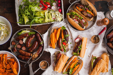 Grill Food party table concept. Grill Sausage Sandwiches with sweet potatoes fried and  sauce served on rustic table. Top view.