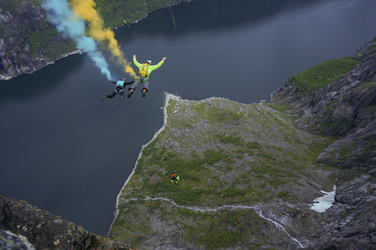 three basejumpers jumping from huge mountain in Norwegian fjord blue and yellow smoke