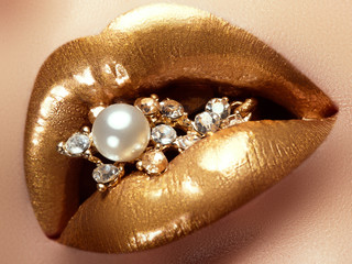 Cosmetics and make-up. Closeup of gold artistic lips. Glitter shiny lip makeup. Shoot of a beautiful girl with golden lipstick and gloss. Sexy and stylish lips. Pearls and diamonds in her mouth