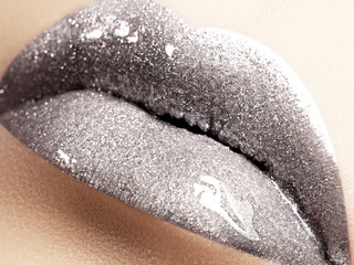 Close-up of liquid silver woman lips with glittering silver. Glittering Lips. Fashion Make-up