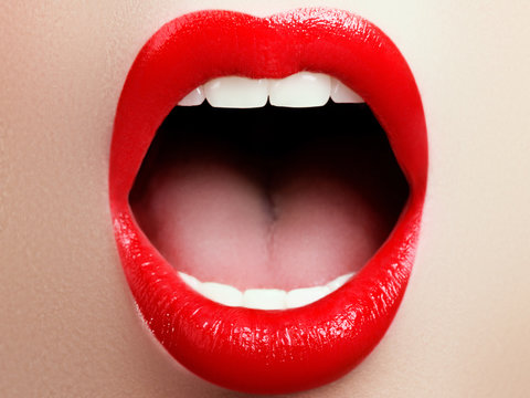 Close-up of woman's lips with fashion red make-up. Beautiful female mouth, full lips with perfect makeup