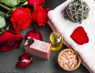 Spa products with roses oil, soap and sea salt.Red roses and soft towels.Top view spa therapy