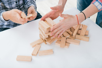 Game of physical and mental skill. Keep balance. girl builds tower of wood blocks. Entertainment activity. Education, development. The girls collect a sprawling constriction of wooden Blocs