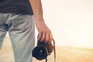 Professional Photographer. Man holding Professional Digital Camera outdoors