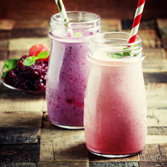 Smoothies from blackberries and strawberries in glass bottle, vintage wooden background, selective focus