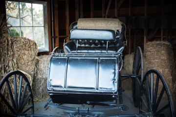 Antique horse carriage in barn on farm