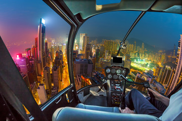 Helicopter cockpit flying on Hong Kong skyscrapers at night in Wan Chai district, Hong Kong island. Fisheye view.