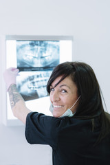 Female doctor dentist looking at x-ray