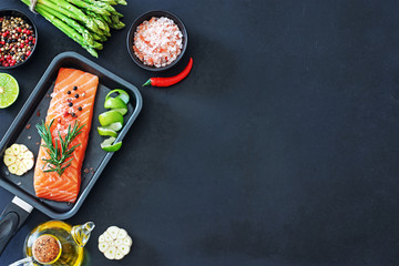 Top view of raw salmon steak in a pan, bunch of green asparagus with spices, salt and oil ready to cook over dark background. Copy space.