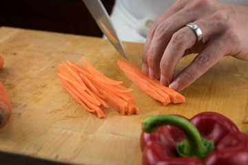 Close Up of Hands Cutting Long Strips of Carrots