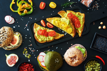 Top view of variety of vegetarian sandwiches and burgers with avocado, radish, cream cheese, figs, pumpkin seeds, pepper and tomato. Healthy snack concept.