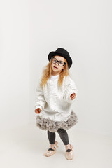 Cute little girl hipster ballerina in a ballet tutu, pointes, glasses and a hat. The younger generation of dancers.