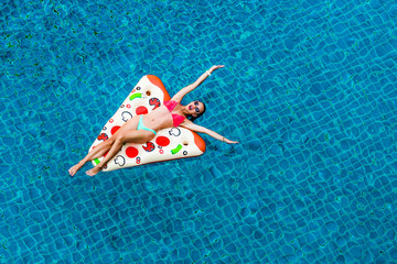 A beautiful bright sexy funny woman is floating on an inflatable pizza in the pool, sunbathing, laughing. Relax on a tropical island in the hotel. Perfect body and healthy skin, hair, view from above